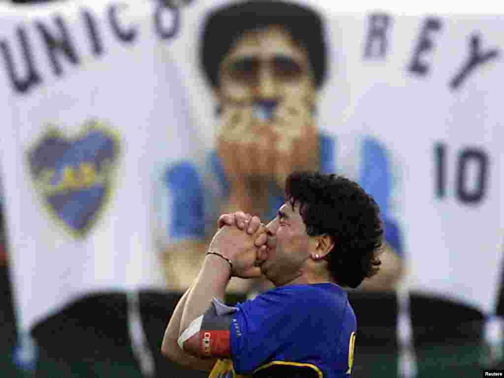 Lenda do futebol argentino, Diego Armando Maradona, vestindo uma camisa do Boca Juniors, agradece aos mais de 50.000 fãs que assistiram ao seu jogo de despedida no estádio do Boca Juniors em Buenos Aires, 10 de novembro de 2001