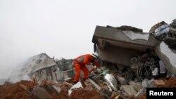 Lính cứu hỏa dùng đèn pin để tìm người sống sót trong đống đổ nát của tòa nhà bị sập sau vụ đất lở ở Thâm Quyến, Quảng Châu, ngày 20/12/2015.