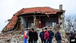 Villagers stand in front of a damaged house after two quakes, both with preliminary magnitudes of 5.3, jolted Turkey's northern Aegean coast, in Yukarikoy village Canakkale province, Monday, Feb. 6, 2017, damaging dozens of homes in at least five villages and injuring several people.