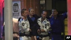 Một con tin bị thương được đưa ra xe cứu thương sau cuộc trấn áp của cảnh sát ở khu vực Martin Place, Sydney, Australia, 16/12/2014.