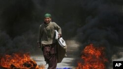 A boy walks past tires set ablaze by protesters following a shootout by unidentified gunmen in Pakistan's southwestern city of Quetta, March 29, 2012.
