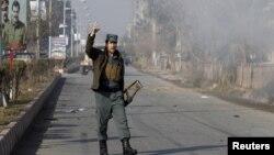 Un policía afgano reacciona al humo que sale del ataque al consulado pakistaní en Jalalabad, Afganistán, el miércoles, 13 de enero de 2016.