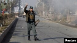 An Afghan policeman reacts as smoke billows during an attack near the Pakistani consulate in Jalalabad, Afghanistan, Jan. 13, 2016.