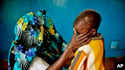 A mass rape victim comforts her son in the town of Fizi, Congo, Feb. 20, 2011.