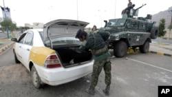 Seorang polisi memeriksa mobil di sebuah pos pemeriksaan dekat Kedubes AS di Sanaa, Yaman (6/8). Keamanan Kedubes AS di Yaman diperketat setelah mendapat ancaman serangan al-Qaeda.