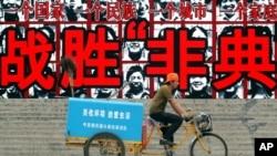 资料照:胡温时期之初,一名清洁工人骑车路过一幅抗击非典的宣传牌。(2003年6月9日)