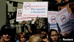 Supporters of Venezuela's President Nicolas Maduro hold placards during a gathering to support Maduro's government order of suspension of CNN's Spanish-language service outside the National Commission of Telecommunications (CONATEL), in Caracas, Venezuela, Feb. 16, 2017.