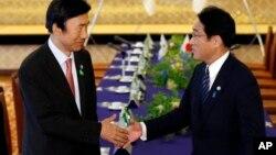 윤병세 한국 외교장관(왼쪽)과 기시다 후미오 일본 외무상이 지난 6월 일본 도쿄에서 회담에 앞서 악수하고 있다. (자료사진)