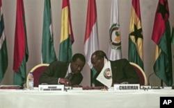 Alassane Ouattara (à dr.) président de la CEDEAO, s'entretient avec l'un des participants au sommet d'Abidjan