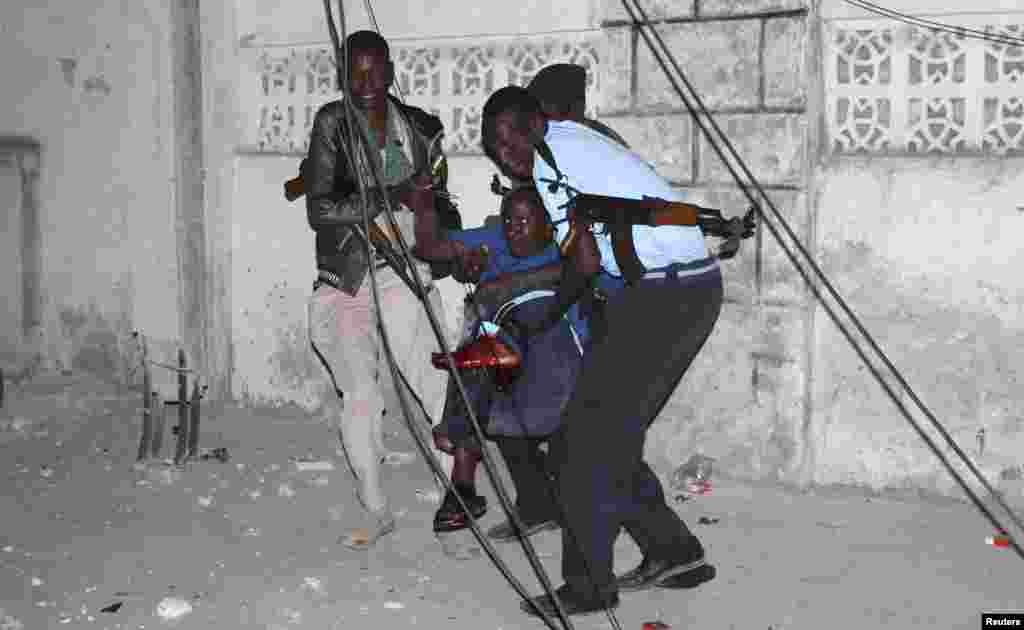 Police officers carry an injured man from the scene of a bomb attack outside the Jazeera Hotel in Mogadishu, Jan. 1, 2014.