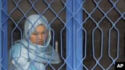 An Afghan inmate watches from behind a barred window during a media event at a women's prison in Kabul. (File Photo - March 30, 2010)