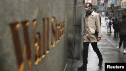 Archivo - Un hombre usando una máscara protectora camina en Wall Street el 13 de marzo de 2020.