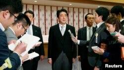 Thủ tướng Nhật Bản Shinzo Abe (giữa) nói chuyện với phóng viên báo chí sau khi viếng đền thờ Yasukuni