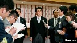 日本首相安倍晋三(中)在参拜东京靖国神社后与媒体见面。(2013年12月26日)