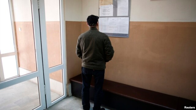 A man looks at a list with job vacancies posted at the entrance of an employment agency in the town of Vratsa, some 110km (68 miles) north of Sofia, Apr. 10, 2013.