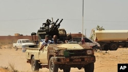 Anti-Gadhafi fighters ride a pick-up truck with an anti-aircraft gun attached to it toward Sirte, September 10, 2011