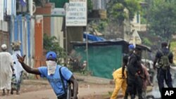 Guinean police carrying automatic weapons clear the mostly Peul suburb of Bambeto in Conakry, Guinea, Tuesday, Nov. 16, 2010, as groups of UFDG youth set up barricades. A de-facto curfew is in effect in the area, residents staying inside, one day after it