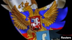 FILE - A Russian flag and a 3-D model of the Facebook logo are seen through a cutout of the Twitter logo in this photo illustration taken in Zenica, Bosnia and Herzegovina, May 22, 2015.