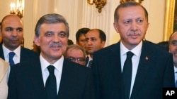 In this Aug. 12, 2014 photo, released by Turkish officials, Turkish President Abdullah Gul, left, and president-elect Recep Tayyip Erdogan stand pose for photos during a farewell reception for Gul in Ankara, Turkey.