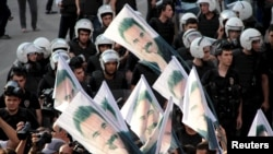 FILE - Demonstrators hold flags with pictures of imprisoned Kurdish rebel leader Abdullah Ocalan, during a protest against latest security operations in Diyarbakir, Turkey, Sept. 6, 2015.