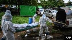 လည္းကူးသုႆန္သို ့ ကိုဗစ္ျဖင့္ေသဆံုးသူတဦးအား ပရဟိတအဖြဲ႕တခုက သယ္ေဆာင္စဥ္ (ဓာတ္ပံု - AFP)