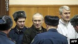 Mikhail Khodorkovsky, giữa, và Platon Lebedev, phải, được hộ tống đến một phòng xử án ở Moscow, 27/12/2010