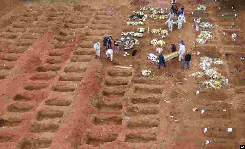 Workers in protective clothing bury three COVID-19 victims at the Vila Formosa cemetery in Sao Paulo, Brazil. Brazil is nearing two million cases of COVID-19 and 75,000 deaths.