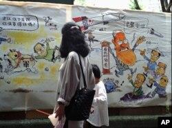 1996年3月23日,台北一个市场上的漫画。左侧漫画上有江泽民。右侧漫画上,台湾总统李登辉(右)安抚他的竞争对手说,他有18套办法对付中国导弹。
