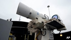 Na fotografiji od 30. jula 2012. vidi se lasersko oružje je privremeno instalirano na američkom razaraču USS Djui u San Dijegu. Mornarica je tada saopštila da planira da ga testira 2014.
