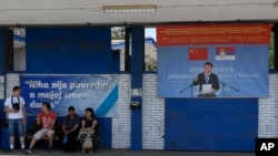 "FILE - Workers rest near billboard showing Chinese President Xi Jinping, reading: ""Welcome President"", right, and billboard reading: ""Nobody was hurt in my shift today"" in front of the Zelezara Smederevo steel mill, in the city of Smederevo, 45 kilometers east of Belgrade, Serbia, June 29, 2017. When U.S. Steel sold its loss-making smelter in Serbia to the government for $1 in 2012, few thought the communist-era factory would ever be revived."