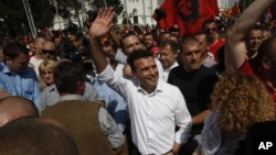 FILE - Zoran Zaev, center, the leader of the opposition social democrats, waves to the supporters during a protest in front of the Government building in Skopje, Macedonia, May 17, 2015.