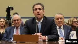 Michael Cohen, the former personal attorney of U.S. President Donald Trump, is flanked by his attorneys Lanny Davis (L) and Mike Monico (R) as he testifies before a House Committee on Oversight and Reform hearing on Capitol Hill in Washington, Feb. 27, 20