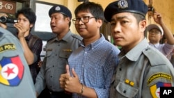 Reuters journalist Wa Lone, center, is escorted by police as he returns to court after a break during their trial, Feb. 1, 2018, outside of Yangon, Myanmar.