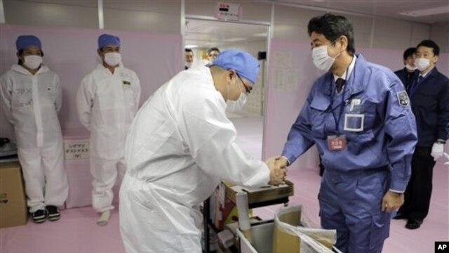 Perdana Menteri Jepang yang baru, Shinzo Abe, di PLTN Fukushima Dai-ichi di Okuma, Prefektur Fukushima, Jepang timur laut (29/12). (AP/Itsuo Inouye)