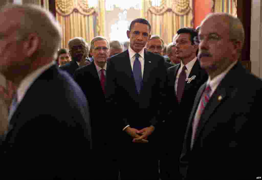 January 25: President Barack Obama stands with Members of Congress in House Speaker John Boehner's ceremonial office as Bill Livingood, House Sergeant at Arms, left, and Terrance Gainer, Senate Sergeant at Arms, right, prepare to escort them onto the floo