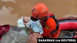 Personel Badan SAR Nasional (Basarnas) mengevakuasi bayi di daerah terdampak banjir di Jakarta, 20 Februari 2021. (Foto: Basarnas via REUTERS)