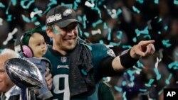 Kvoterbek Filadelfija Iglsa Nik Fols (9) drži ćerku Lili Džejms, posle pobede u 52. NFL Superboulu u Mineapolisu, 4. februara 2018.