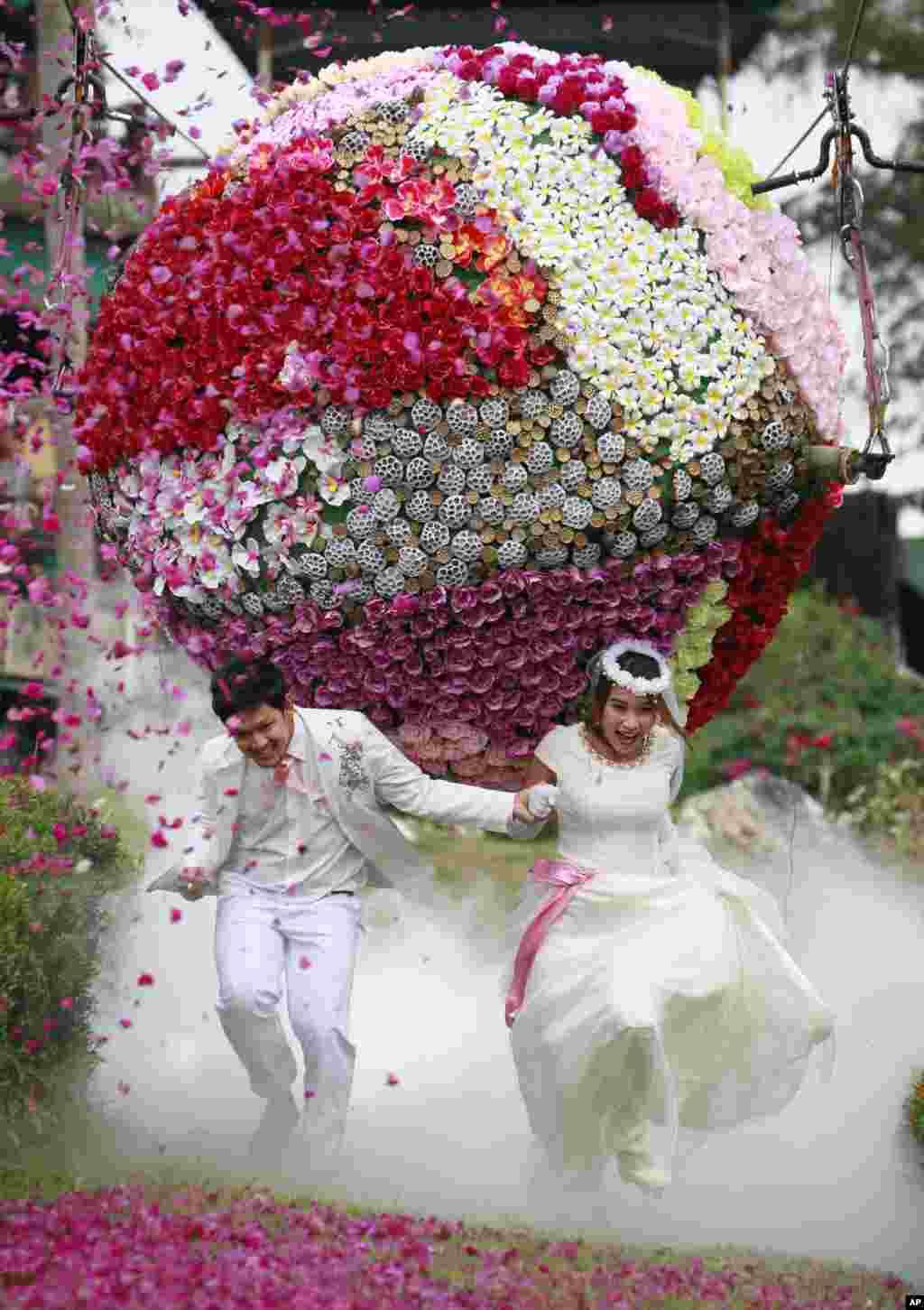 Pasangan pengantin baru: Prasit Rangsitwong (kiri), dan Varutton Rangsitwong berlari menghindari bola raksasa yang dibuat dari bunga-bunga, sebagai bagian dari perayaan acara pernikahan mereka di provinsi Prachinburi, Thailand, yang dilangsungkan pada malam menjelang hari kasih sayang atau Valentine's Day.