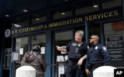 FILE - Two officers are seen outside the entrance to the Immigration and Customs Enforcement office in San Francisco, Feb. 28, 2018.