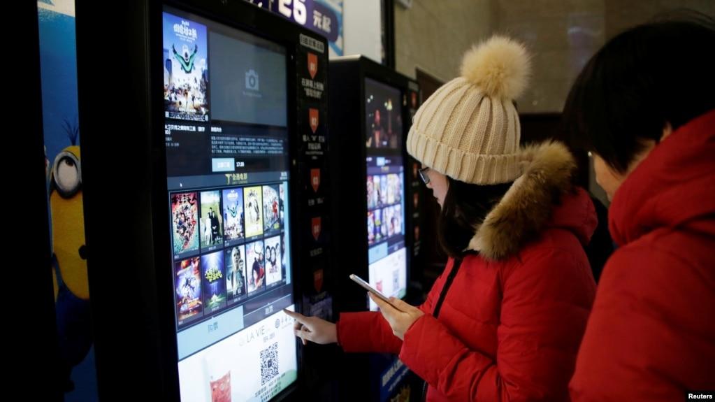 人們在天津一家影院的自動售票機前印電影票。 (資料照)