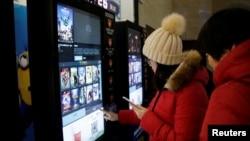 大眾在天津一家影院自動售票機前印電影票 (資料圖片)