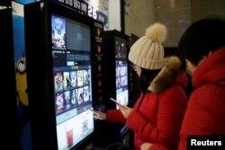 지난 1월 중국 톈진의 한 극장에서 관람객들이 자동매표기를 이용해 영화표를 구입하고 있다.