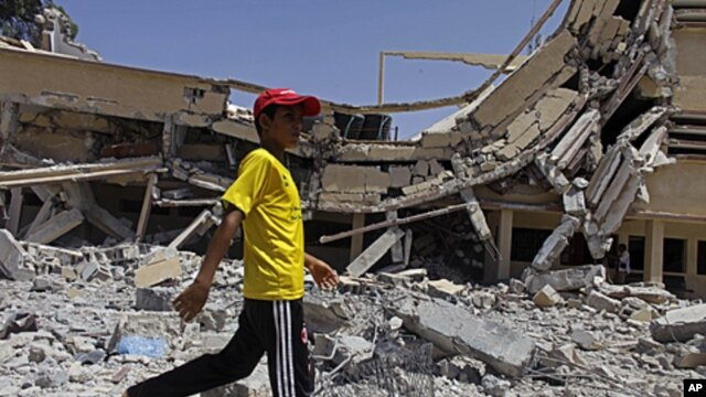 In this photo taken on a government-organized tour a child walks past the rubble of a university building in Zlitan, Libya, August 4, 2011