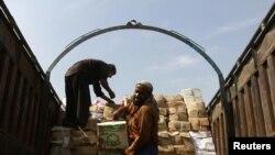 افغان مزدور ٹرک سے سامان اتار رہے ہیں (فائل فوٹو)