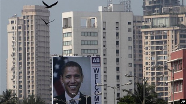 Birds fly past a billboard depicting U.S. President Barack Obama in Mumbai, India, Friday, Nov. 5, 2010. President Obama is scheduled to visit the city during his trip to India.