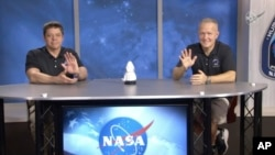 In this frame grab from NASA TV video, astronauts Bob Behnken, left, and Doug Hurley wave during a news conference, Tuesday, Aug. 4, 2020, in Houston. (NASA TV via AP)