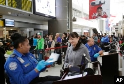 FILE - A TSA officer, left, checks a passenger's ticket, boarding pass and passport as part of security screening at John F. Kennedy International Airport.