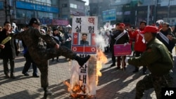 FILE - A member of a South Korean conservative group kicks a burning banner with an image of North Korean leader Kim Jong Un and North Korean flags during a rally denouncing the North, in Paju, South Korea, Jan. 11, 2016.