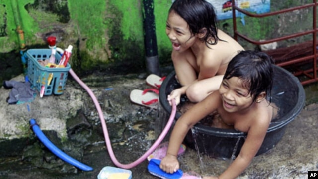 Informal settlers play while bathing on a tub in San Juan, Manila. The Philippines is expected to sustain post-crisis economic growth, but this will be without development which may increase poverty, according to a new study from the United Nations, May 2