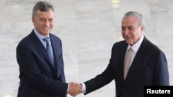 Argentine's President Mauricio Macri (L) is greeted by his Brazilian counterpart Michel Temer before their meeting at the Planalto Palace in Brasilia, Brazil, Feb. 7, 2017.